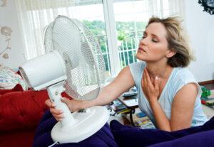 women in front of a desk fan